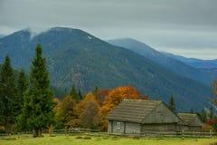 Casas simples velhas de madeira em um esclarecimento entre árvores amarelas e montanhas verdes Fotos de Stock