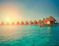 Casas sobre la agua de mar reservada transparente en una puesta del sol, entonando maldives imagen de archivo