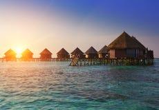 Casas sobre la agua de mar reservada transparente en una puesta del sol maldives fotografía de archivo libre de regalías