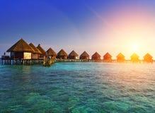 Casas sobre la agua de mar reservada transparente en una puesta del sol maldives foto de archivo libre de regalías
