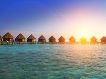 Casas sobre la agua de mar reservada transparente en una puesta del sol maldives imagenes de archivo