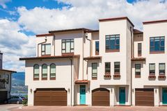 Casas urbanas residenciales con la opinión del paisaje sobre un lago y las montañas Casas urbanas en hileras con la puerta ancha  foto de archivo libre de regalías