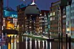 Casas urbanas viejas en el canal en Hamburgo por noche fotografía de archivo