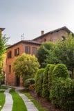 Casas velhas com telhados telhados e torretas contra um céu nebuloso em Milão, Itália imagens de stock royalty free