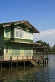 Casas verdes de madera viejas en la orilla Foto de archivo libre de regalías