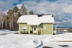 Casas verdes en bosque de la nieve Imagen de archivo libre de regalías
