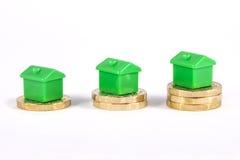 Casas verdes que se sientan encima de monedas imágenes de archivo libres de regalías