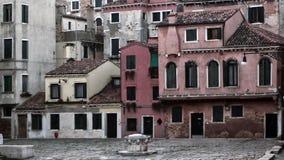 Casas vermelhas desvanecidas velhas em um quadrado em Veneza com obturadores Fotos de Stock Royalty Free