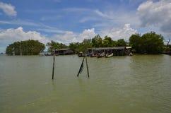 Casas y barcos con los árboles del mangle en el mar Imagen de archivo libre de regalías