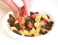 Casca cristalizada, raisins, e mão das mulheres. Imagem de Stock
