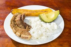A casca da carne de porco, arroz, fritou a banana e o abacate - prato colombiano típico Vista superior imagens de stock