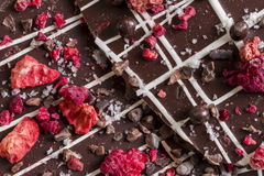 Casca escura do chocolate com frutos e as porcas secados Fotos de Stock