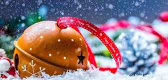 Cascabeles de las bolas de la Navidad Cinta roja con feliz Navidad del texto Fondo y decoración del extracto Nevado Fotografía de archivo