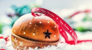 Cascabeles de las bolas de la Navidad Cinta roja con feliz Navidad del texto Fondo y decoración del extracto Nevado Imágenes de archivo libres de regalías