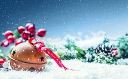Cascabeles de las bolas de la Navidad Cinta roja con feliz Navidad del texto Fondo y decoración del extracto Nevado imagenes de archivo