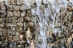 Cascada artificial La corriente del agua cae abajo delante de la imitación antigua de la pared de ladrillo Fotos de archivo