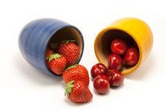 Cascada de fresas y de cerezas rojas de rubíes Fotografía de archivo libre de regalías