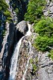 Cascada de la montaña que fluye abajo del acantilado rocoso Fotografía de archivo libre de regalías