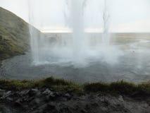 Cascada de Seljalandfoss en Islandia, según lo visto derecho de detrás el agua que cae fotos de archivo libres de regalías