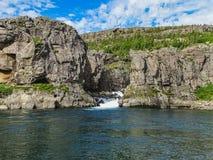 Cascada de Sveinsstekksfoss en los fiordos del este en Islandia foto de archivo
