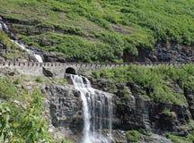 Cascada debajo de un camino en Parque Nacional Glacier Fotografía de archivo