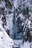Cascada del invierno entre las rocas nevosas Fotos de archivo