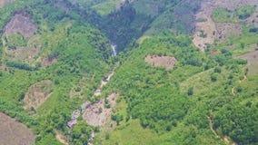 Cascada distante de la visión panorámica entre Hilly Lands con las plantas metrajes