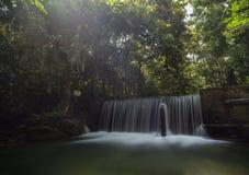 Cascada en el bosque con el rayo de la luz en la exposición larga Foto de archivo