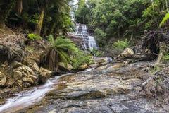 Cascada en la selva tropical que fluye abajo de la formación de roca Foto de archivo