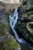 Cascada entre dos rocas en el bosque Foto de archivo libre de regalías