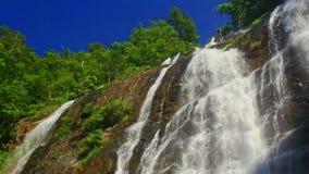 Cascada espumosa de la cascada del río de la montaña del primer en las zonas tropicales almacen de video