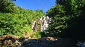 Cascada espumosa de la cascada del río de la montaña en las zonas tropicales almacen de metraje de vídeo