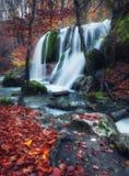 Cascada hermosa en bosque del otoño en montañas crimeas en el sol Fotos de archivo libres de regalías