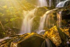 Cascada hermosa en rayos del sol imagenes de archivo
