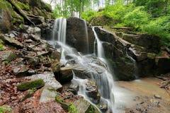 Cascada hermosa entre las rocas enormes en bosque foto de archivo