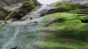Cascada hermosa sobre piedras cubiertas de musgo en la ensenada de Tintagel en Cornualles metrajes