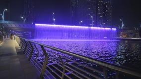 Cascada iluminada colorida La cascada es parte del desarrollo del canal del agua de Dubai almacen de video
