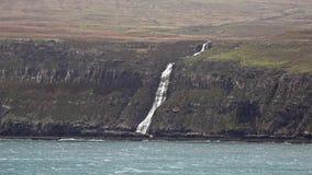 Cascada a la izquierda parada e invertida por la tormenta Callum del otoño en los acantilados vistos de un Milovaig más bajo - is almacen de video