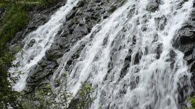 Cascada a lo largo de la roca rugosa metrajes