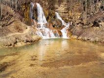 cascada Mineral-rica en aldea afortunada fotografía de archivo