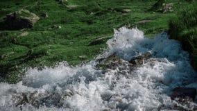 Cascada que cae abajo al prado hermoso del verde de la montaña Foto de archivo libre de regalías