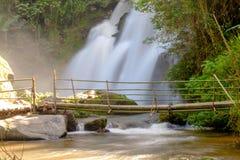 Cascada que fluye abajo de las calas, que un puente de madera hizo fuera de bambú Imágenes de archivo libres de regalías