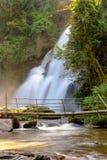 Cascada que fluye abajo de las calas, que un puente de madera hizo fuera de bambú Fotografía de archivo libre de regalías