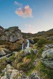 Cascada que fluye Blurred en las montañas con el cielo y las nubes coloridos en el crepúsculo, entre rocas, los cantos rodados y  Imágenes de archivo libres de regalías