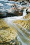Cascada que fluye sobre rocas Imagenes de archivo