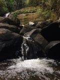 Cascada que fluye sobre rocas enormes Foto de archivo
