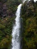 Cascada que se derrama sobre alta cara del acantilado Foto de archivo libre de regalías