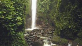 Cascada tropical que fluye de la montaña rocosa en paisaje aéreo de la selva tropical Muchacha del viajero en la cascada rocosa a metrajes