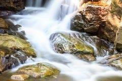 Cascada y rocas cubiertas con el musgo Imagenes de archivo