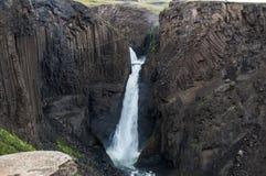 Cascadas majestuosas con las rocas y la hierba alrededor Fotografía de archivo libre de regalías